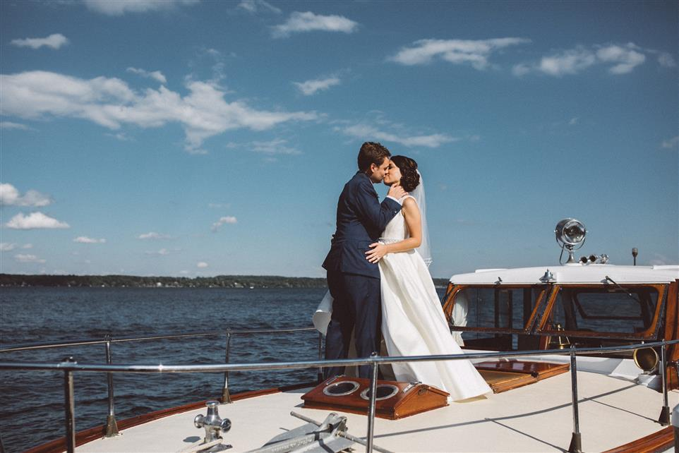 Groom and bride kissing on the water