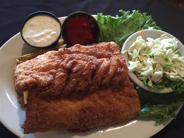 fried fish with a side of coleslaw and dipping sauces