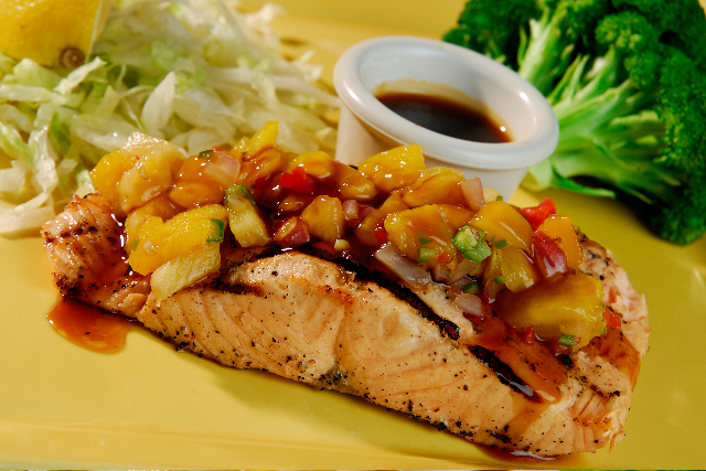 Seared fish topped with vegetables. served with sauce