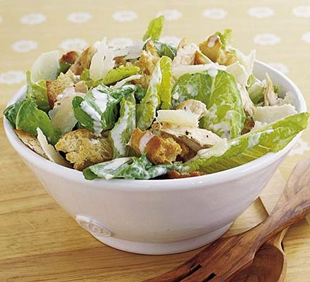 salad topped with croutons and dressing in a bowl