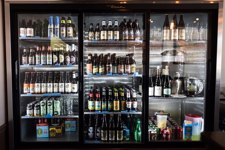 a variety of beer bottles in a refridgerator
