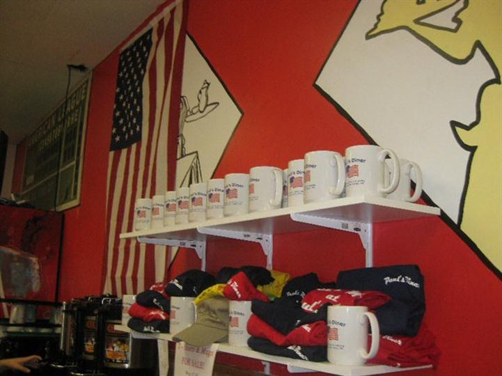 Interior shot of the restaurant's wall with a USA flag, cups, t-shirts, and hats