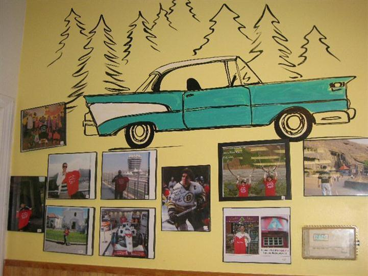 Interior shot of the restaurant's yellow wall with several photos and a green car drawing