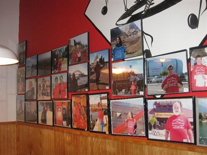 Interior shot of the restaurant's red wall with several photos