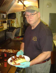 A man in the restaurant's kitchen holding a breakfast plate posing for a photo