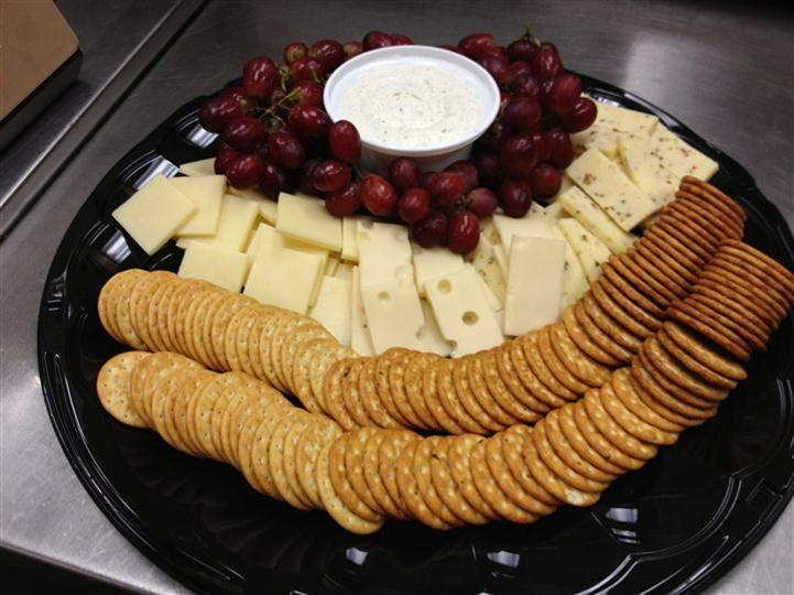 Grapes and cheese platter with white dipping sauce and crackers