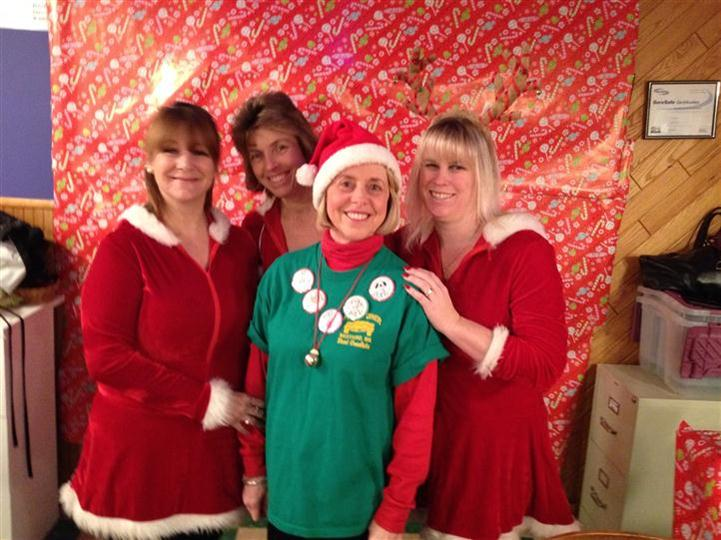 Four smiling women in the restaurant at Christmas posing for a photo