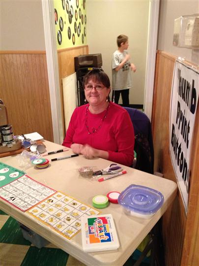 A smiling woman at a thumbprint buttons desk posing for a photo