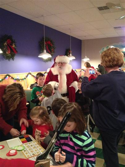 Photo of a Santa Claus giving gifts to children in the restaurant
