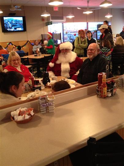 Interior shot of a Santa Claus siting at a table with other people