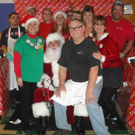 the restaurant's crew with Santa Claus posing for a photo