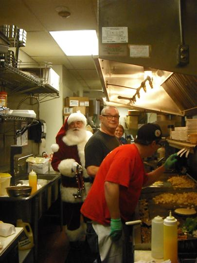 Interior shot of a Santa Claus in the kitchen with the cooks
