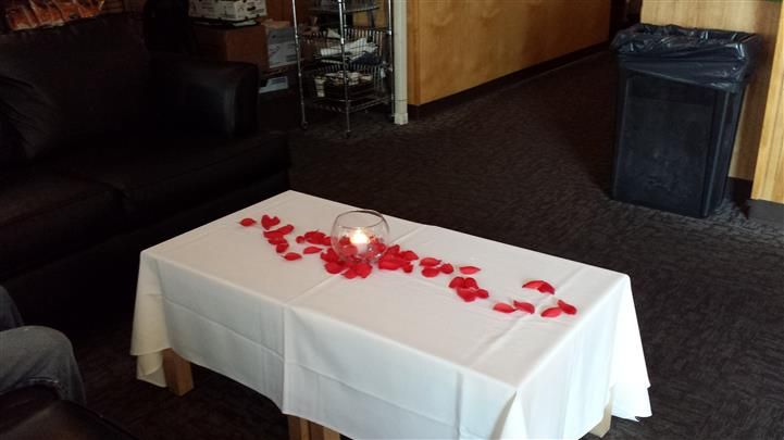A table decorated with table cloth and rose petals
