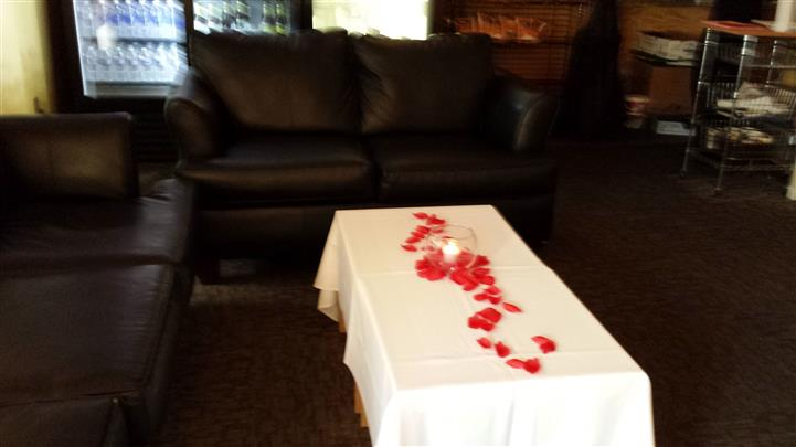 A table decorated with white table cloth and red rose petals