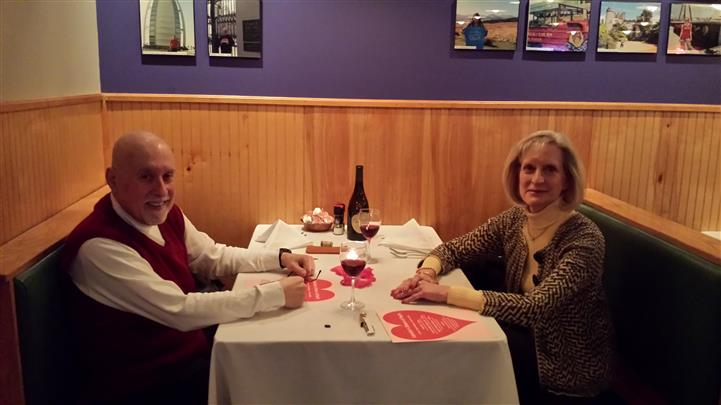 Interior shot of a couple sitting at a table with Valentine's day decoration
