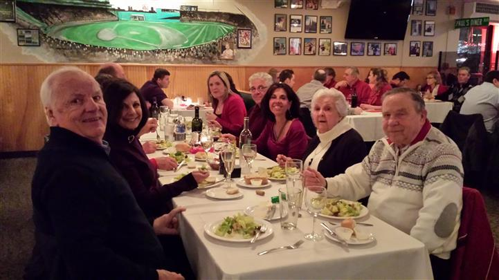 People sitting at the restaurant's table posing for a photo