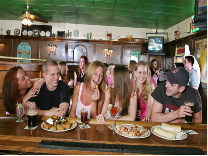 People smiling and socializing at a bar