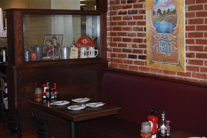 Dining booth in fornt of a red brick wall and right next to a glass cabinet with paraphernalia