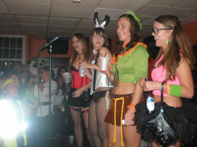 Young girls dressed in costumes in front of a mic posing for photo