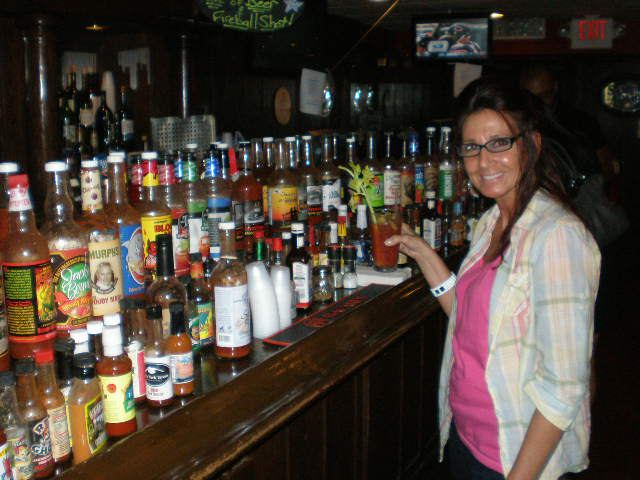 Young girl holding a drink in front of the liquor display at the bar
