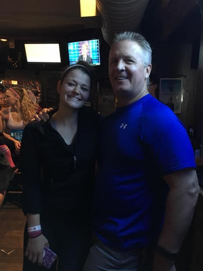 Man and woman in the bar smiling and posing for photo