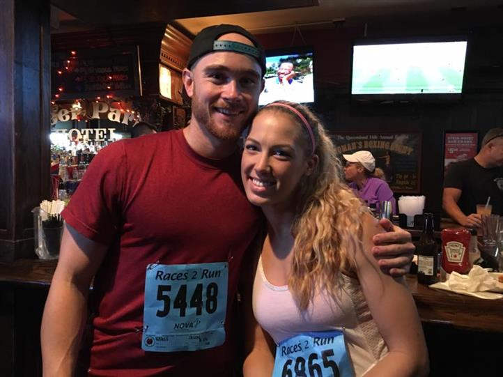 Young man and woman in athletic clothes posing for photo in front of the bar counter