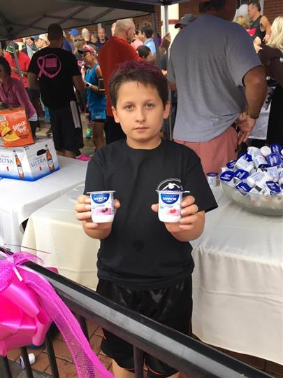 Little boy holding two cups of yogurt and posing for photo