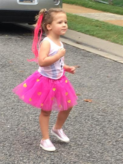Little girl dressed in tulle pink skirt on the street walking