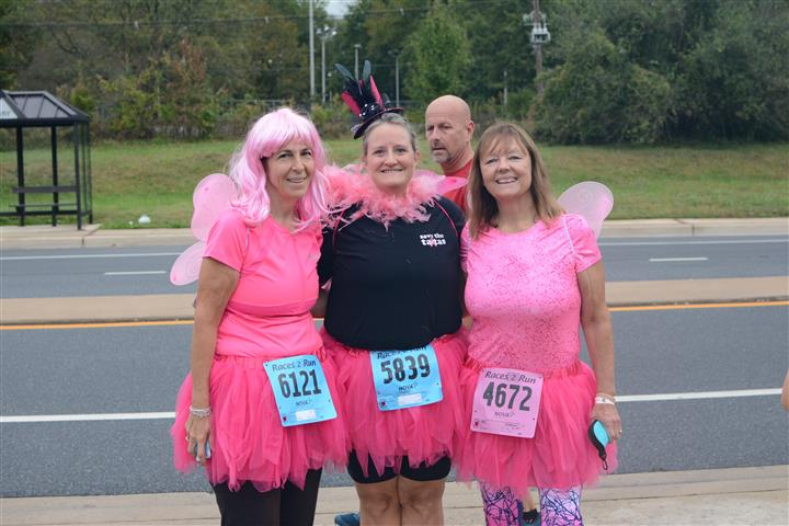 Women wearing pink butterfly wings on their backs and pink tutu skirts posing for photo