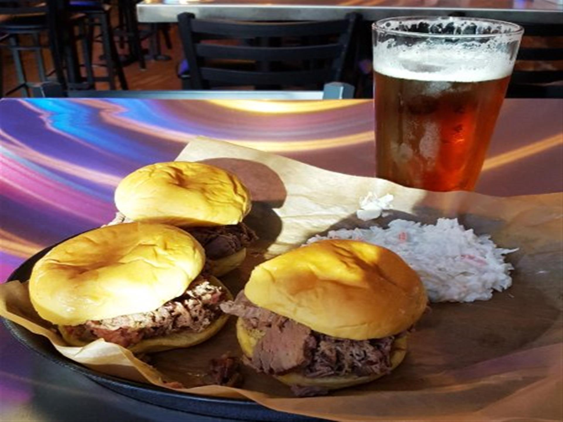 Brisket / pork sandwiches with coleslaw on tray with full beer glass on counter.