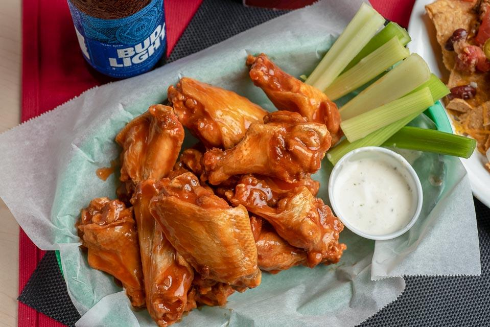 Chicken wings covered in buffalo sauce with a side of celery