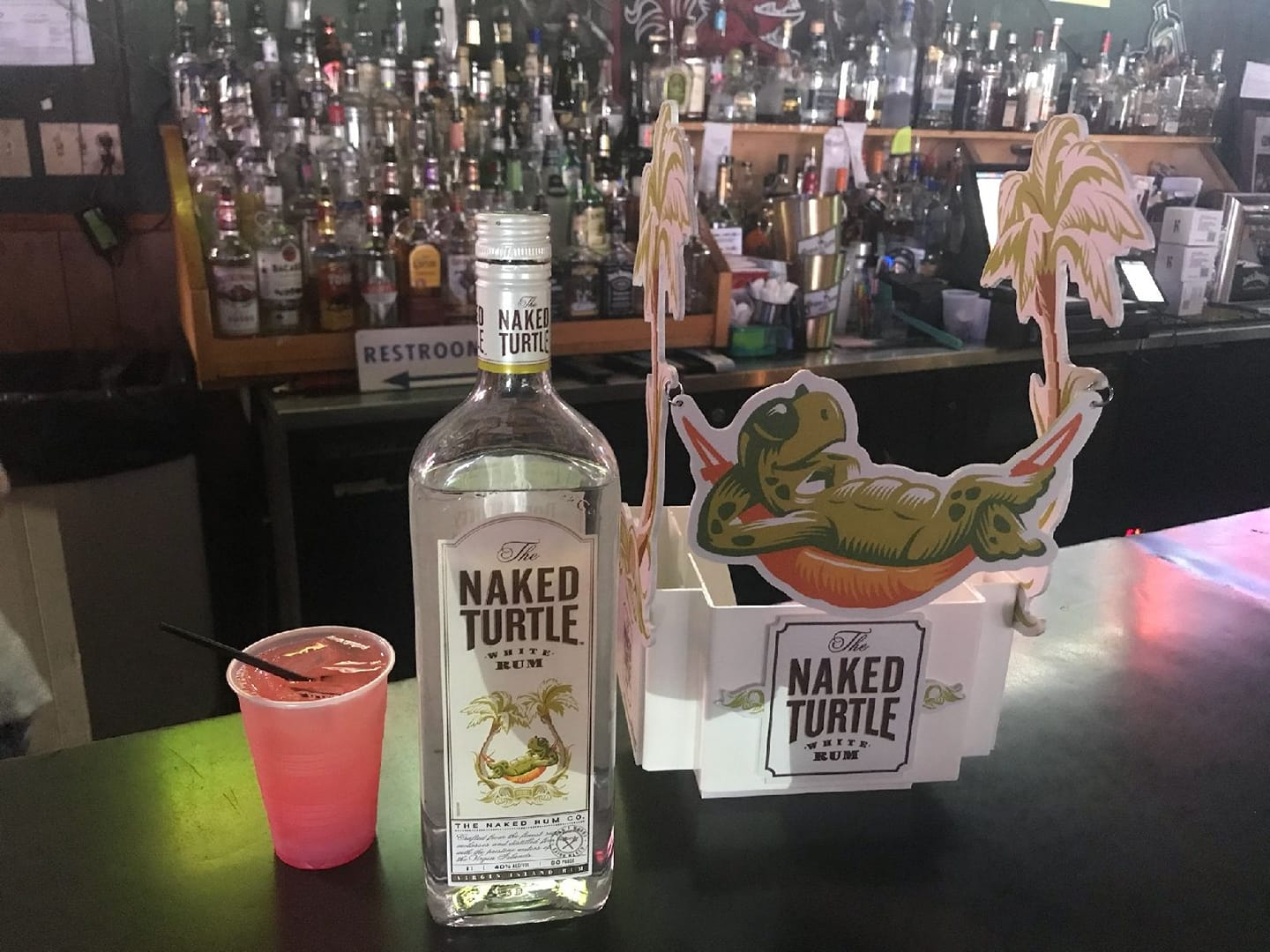 Naked turtle liquor bottle next to cocktail