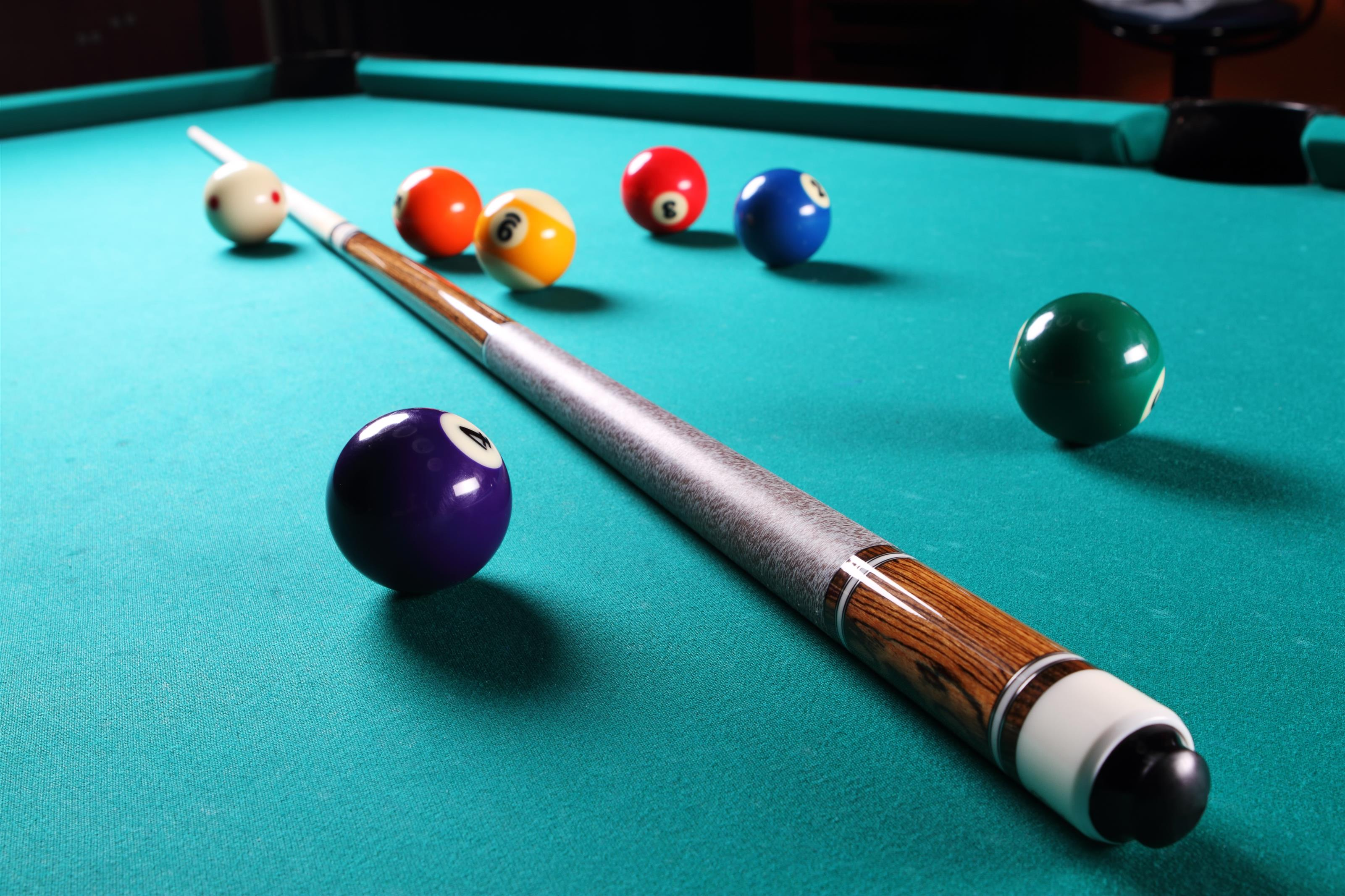 Billiard stick laying on billiard table surrounded by scattered balls