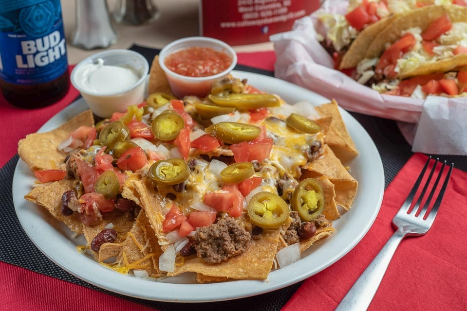 Nachos topped with beef, beans, cheese, tomatoes, jalapenos with a side of dipping sauce