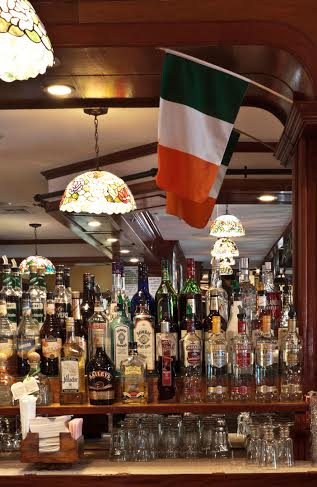 bottles of liquor behind the bar with an irish plag