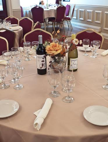 a table with a white tablecloth and 8 chairs and place settings