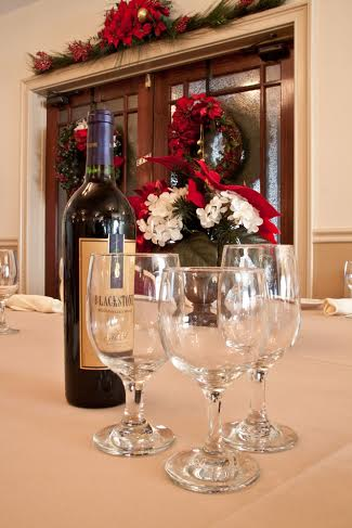 Wine bottle with three glasses on table with christmas decor. Wreaths and christmas garnish on door behind table.