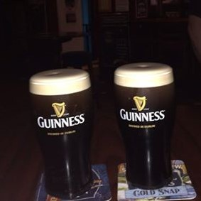 2 full glasses of Guinness with foam at the tops in Guinness branded mugs