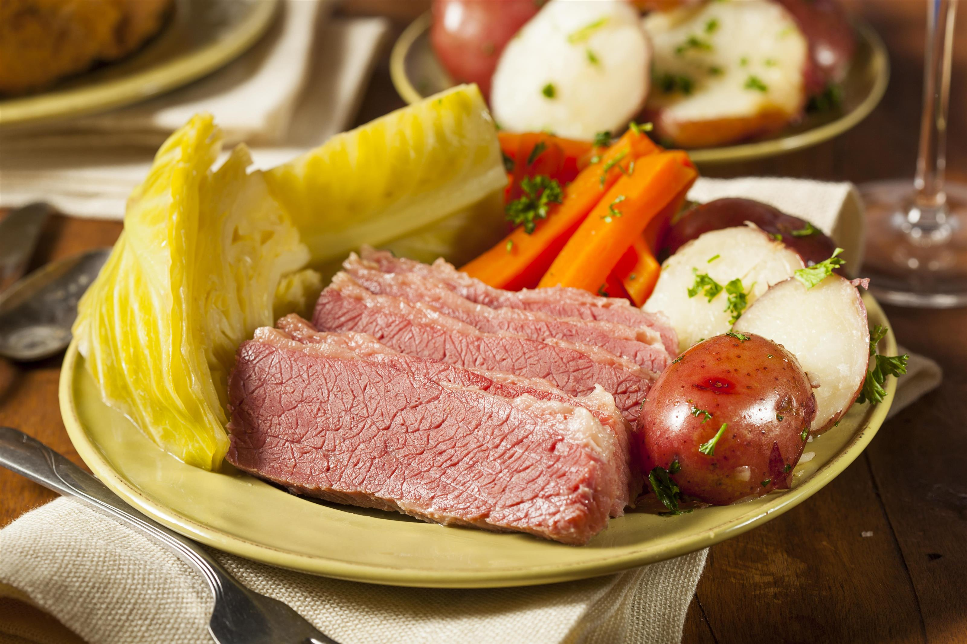 Dish of meat, and carrots, potatoes and cabbage surrounded by other plates with the same food