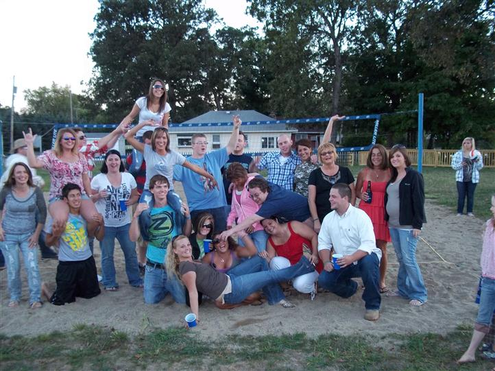 Photo of people posing for a photo in a volley ball court