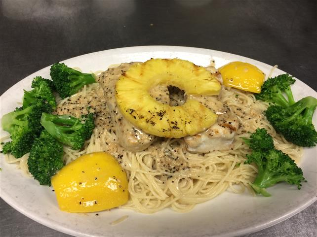Grilled chicken topped with pineapple over pasta.