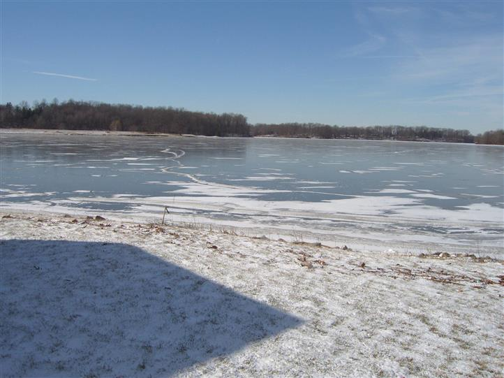 Body of water with snow on the ground