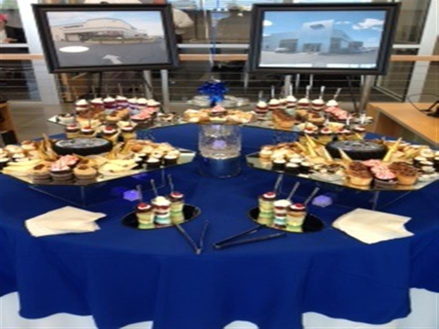 dessert station with a variety of items on top of a blue tablecloth