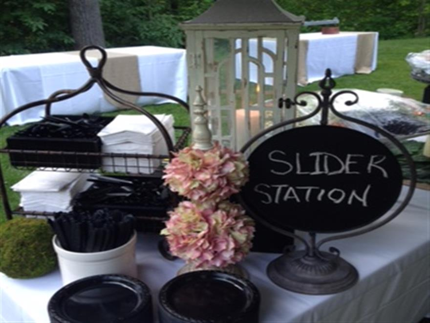 Rustic decorated station with pink flowers, black plating, and a candle lit