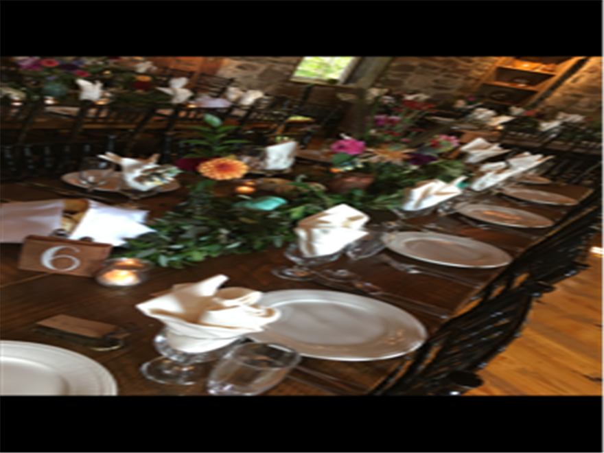 table set for guests with flowers, candles,  napkins, plates, and silverware