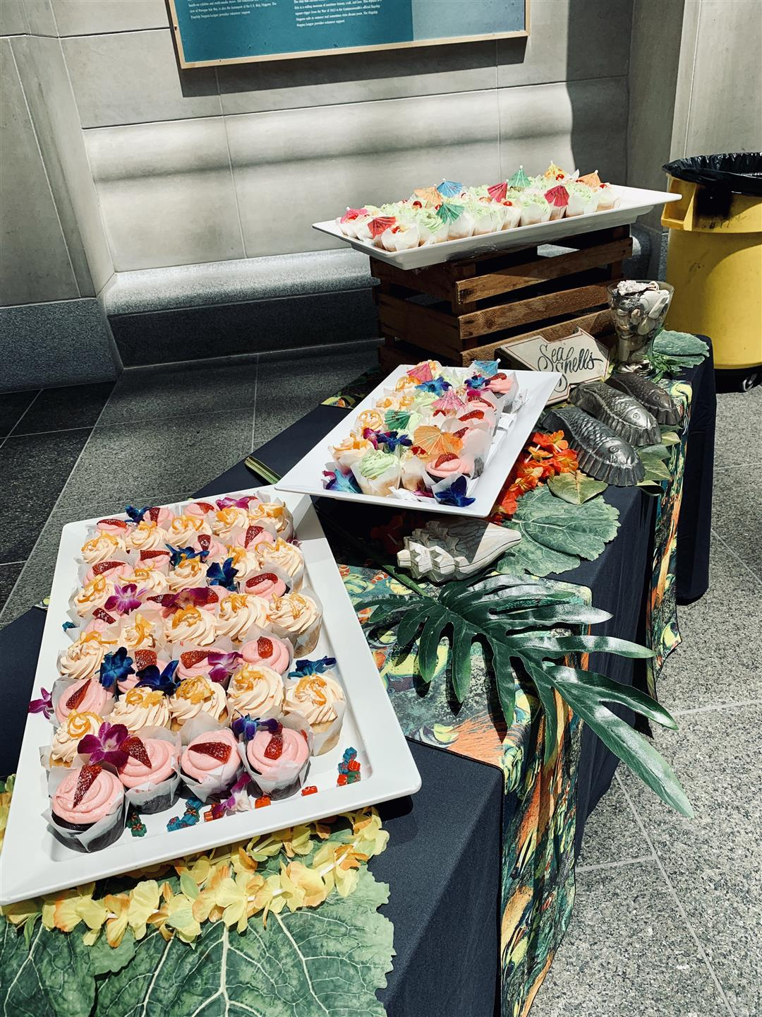 cupcakes displayed on a wooden crate and on a black table cloth with tropical decorations