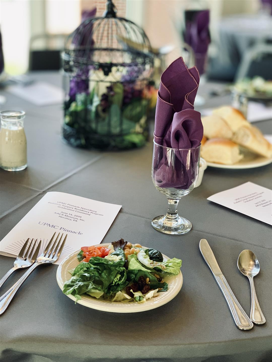plate with salad on it. wine glass with purple napkin inside, and a menu pinned underneath silverware