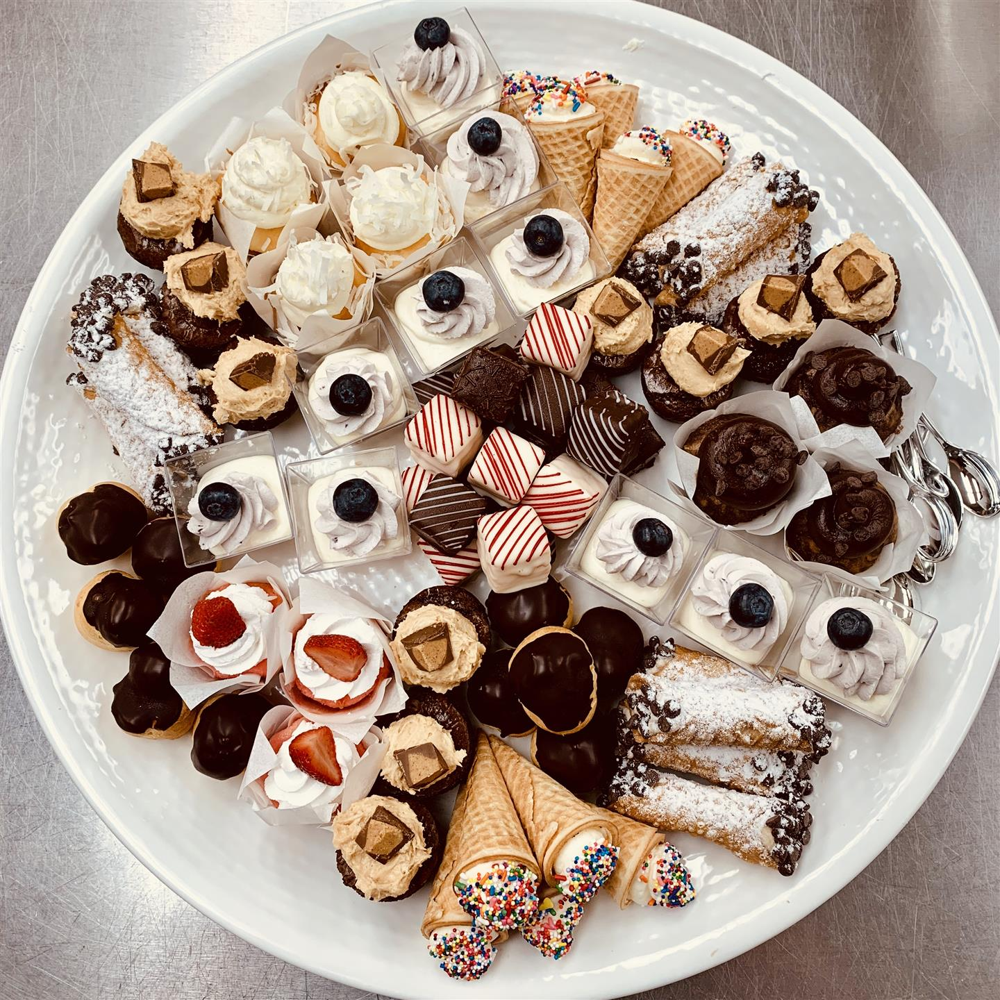 various desserts displayed on a tray including cupcakes, cannolis, and icecream cones