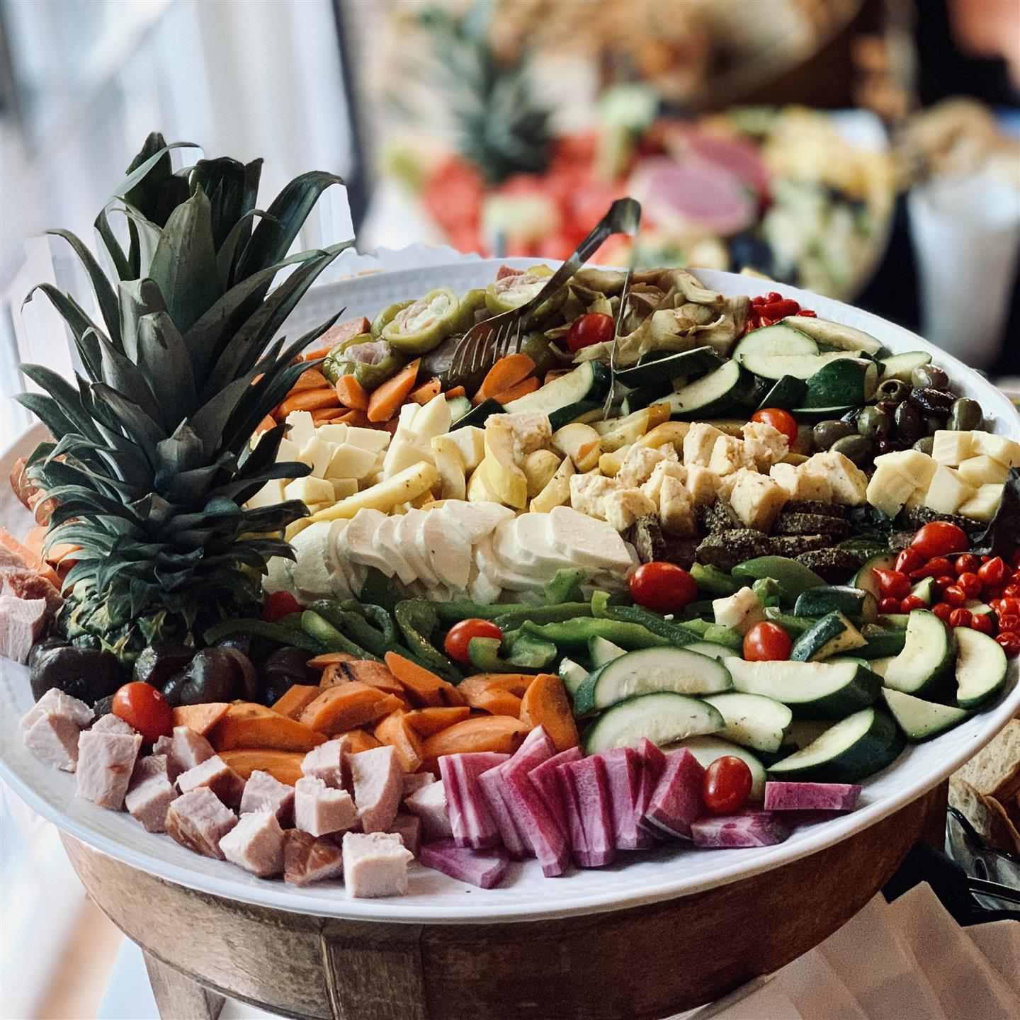 platter with grilled vegetables, cheeses, and meat with a pineapple head on the side