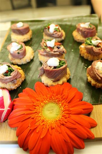 hors d'oeuvres with meat, sour cream, lettuce on tartlet